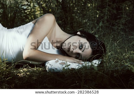 Pale woman in white dress lying on the ground, fairytale scene