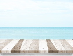 Pale wood plank table top with blurred sea and blue sky at background, Mock up template for display or montage of your product, Summer holiday concept