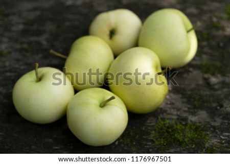 Pale yellow apples on a dark wooden surface.Pale yellow apples on a dark old  wooden table. #1176967501