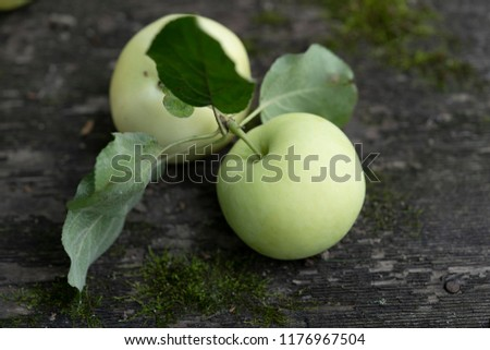 Pale yellow apples on a dark wooden surface.Pale yellow apples on a dark old  wooden table. #1176967504