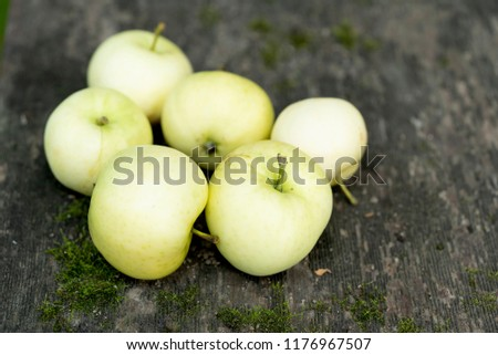 Pale yellow apples on a dark wooden surface.Pale yellow apples on a dark old  wooden table. #1176967507