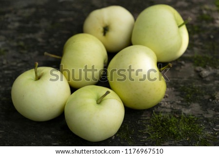Pale yellow apples on a dark wooden surface.Pale yellow apples on a dark old  wooden table. #1176967510