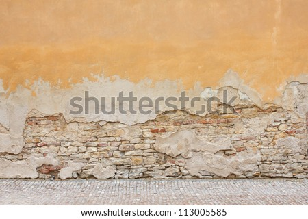 Pale yellow broken plastered wall with brickwork showing through. Background.