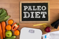 PALEO DIET Fitness and weight loss concept, dumbbells, white scale, fruit and tape measure on a wooden table, top view,