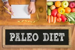 PALEO DIET notebook with fresh vegetables and  on a wooden table,