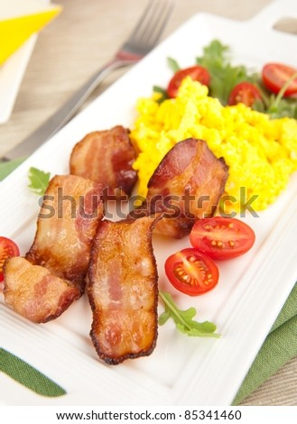 Paleo Style Breakfast of Bacon, Scrambled Eggs, Tomatoes and Arugula Salad