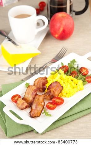 Paleo Style Breakfast of Bacon, Scrambled Eggs, Tomatoes and Arugula Salad - stock photo