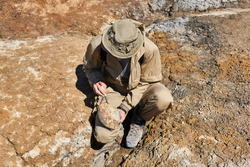 paleontologist holding and brushes a rounded ovoid fossil resembling an dinosaur egg in a desert