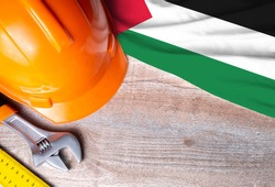 Palestine flag with different construction tools on wood background, with copy space for text. Happy Labor day concept.