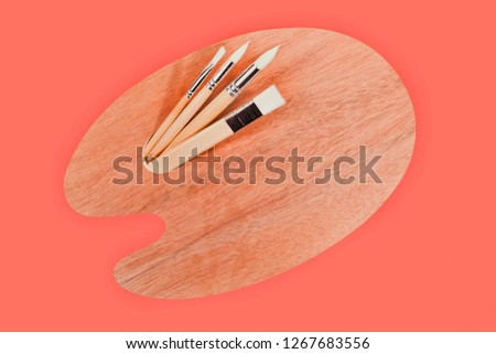 Palette and brushes isolated on living coral background. Pantone color of the year 2019. #1267683556