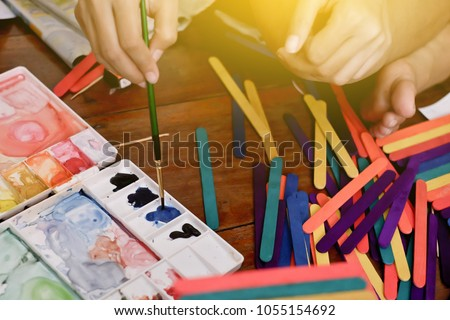 Palette And paintbrush.mix watercolors. The stick is colorful. Children use paintbrush handle to paint.concept: art work, draw,Handmade , DIY