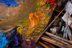 Palette artist table workplace for mixing oil paint. Close-up tools with tubes and brushes. Mix colors mess chaos real life. Creative atmosphere. Artist's Studio draw