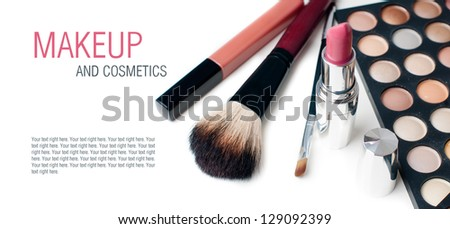Palette of colorful eyeshadows, lipstick and makeup brushes, close-up, isolated