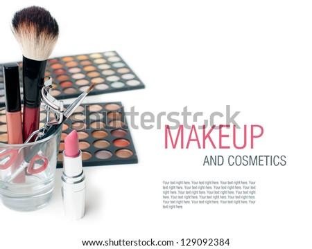 Palette of colorful eyeshadows, lipstick, eyelash curlers and  make-up brushes, close-up, isolated