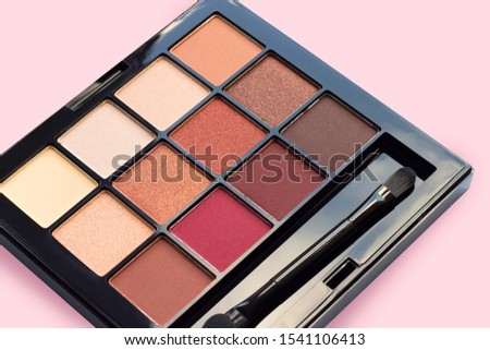 Palette of eyeshadows in brown tones, matte and shimmer eyeshadows on a pink background, close up. Autumn eyeshadow palette, female decorative cosmetics