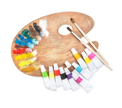 palette with tubes of paint and brushes on a white background