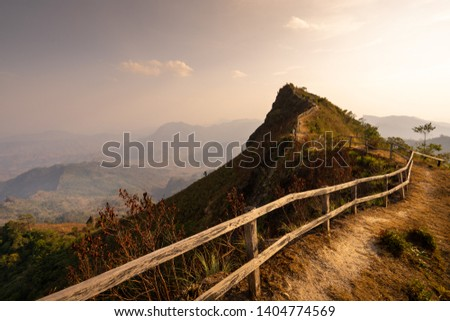 paling fence to peak of the mountain with sunset, Golden sky, in chiangrai, Phuchidao #1404774569