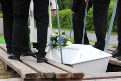 Pallbearers putting down the coffin at a funeral