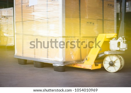 Pallet goods with manual forklift, transport by truck.