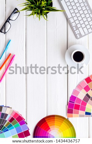 Pallet, keyboard, glasses, cup of coffee and tools for designer work on white desk background top view copyspace frame