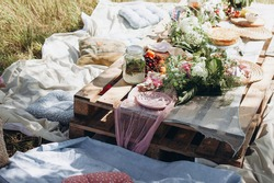 pallet table in the park. decorated festive table in nature. outdoor summer picnic. boho style wedding table
