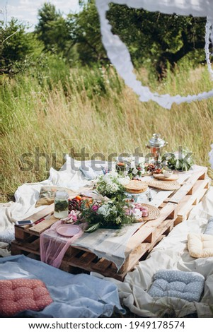 pallet table in the park. decorated festive table in nature. outdoor summer picnic. boho style wedding table Photo stock ©