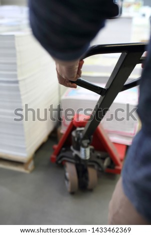 Pallet truck, the worker loads the pallets onto the trolley. #1433462369