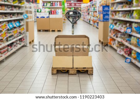 Pallet truck with carton boxes in supermarket store