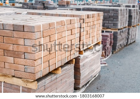 pallets and packages of freshly produced red bricks in a construction warehouse on the street. Concept of repair and building materials Сток-фото ©