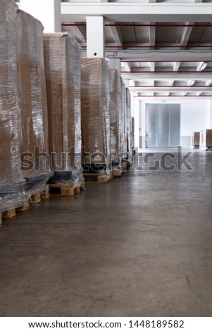 Pallets with cartons and packaging foil are stored in a clean storage room.