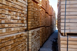 Pallets with wooden bars, a large warehouse of boards. Piles of wooden boards in the sawmill, planking. Warehouse for sawing boards on a outdoors. Wood timber stack blanks construction material.