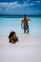 Palm Beach Aruba Caribbean, white long sandy beach with palm trees at Aruba Antilles, couple man and woman mid age on a white beach with palm trees