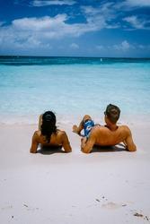 Palm Beach Aruba Caribbean, white long sandy beach with palm trees at Aruba Antilles, couple man and woman mid age on a white beach with palm trees
