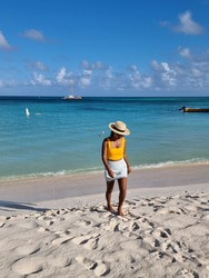 Palm Beach Aruba Caribbean, white long sandy beach with palm trees at Aruba Antilles, woman relaxing on the beach