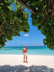 Palm Beach Aruba Caribbean, white long sandy beach with palm trees at Aruba Antilles, young man mid age on the beach in swim short relaxing
