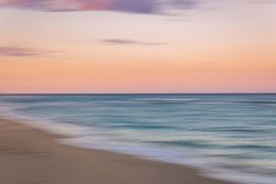 Palm Beach Island beach sunset with slow shutter pan of pink, blue and purple skies with green ocean water