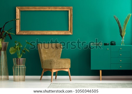 Palm leaf on a modern, teal sideboard with drawers in a luxurious, green living room interior with golden decorations and an upholstered chair #1050346505