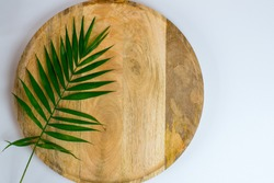 Palm leaf on wooden tray on white background. Place for text. Blank white business card mockups on wooden plate. Wooden backgound with palm leaf. Modern template. Flat lay, top