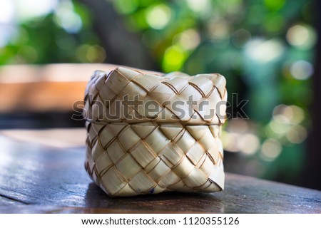 Palm leaves weaving, Thai sticky rice container, on wooden table in home kitchen or resturant, keep rice warm. Natural product, reuse and environmental friendly and safety material. #1120355126
