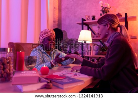 Palm reading. African american plump fortune-teller wearing a huge ring reading the clients palm