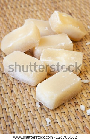 Palm sugar cubes, over bamboo background.