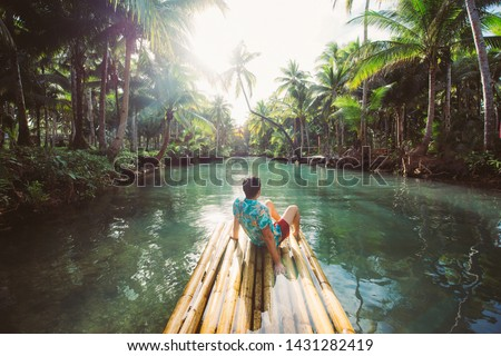 Palm tree jungle in the philippines. concept about wanderlust tropical travels. swinging on the river. People having fun ストックフォト ©