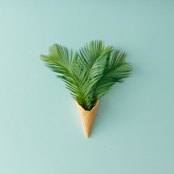Palm tree leaves in ice cream cone on pastel blue background. Flat lay. Summer tropical concept.