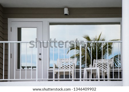 Palm tree reflecting on a patio window with lawn chairs #1346409902