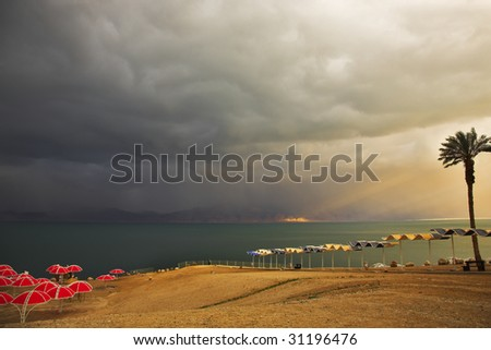Palm trees and beach canopies on a beach of the Dead Sea in a thunder-storm