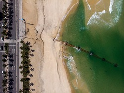Palm trees and boulevard with a large rusty pipeline exposed on the beach of Ipanema after a strong tidal wave washed away a lot of the beach sand. Aerial top down graphical view.