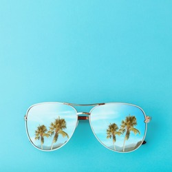 Palm trees and mountains are reflected in sunglasses. Concept on the theme of vacation and travel with copy space