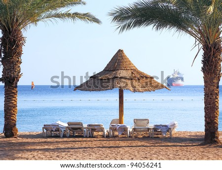 Palm trees and umbrella beach on the perfect sandy beach of the Red sea (Eilat, Israel)