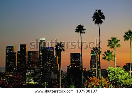 Palm trees at sunset above Los Angeles skyline