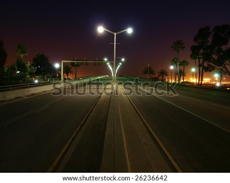 Palm trees line an open California highway at night.